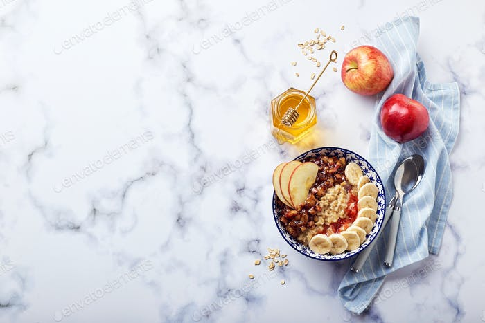 Homemade oatmeal for breakfast with apple, cinnamon and honey