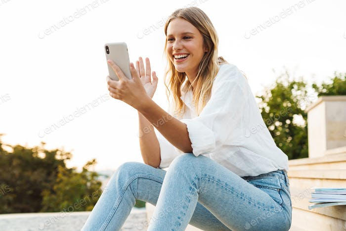Nice woman waving hand and using mobile phone while sitting on staircase