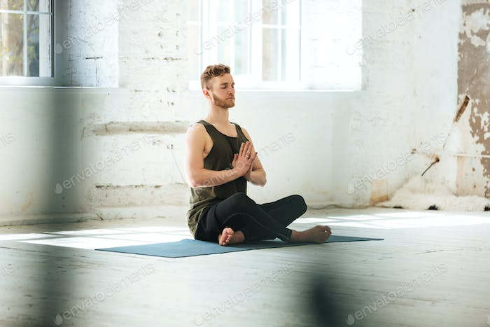 Young candid man sitting on a fitness mat