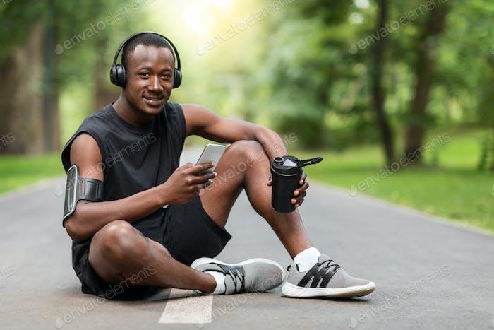 Afrikanischer Sportler sitzen auf Parkweg, trinken und mit dem Smartphone