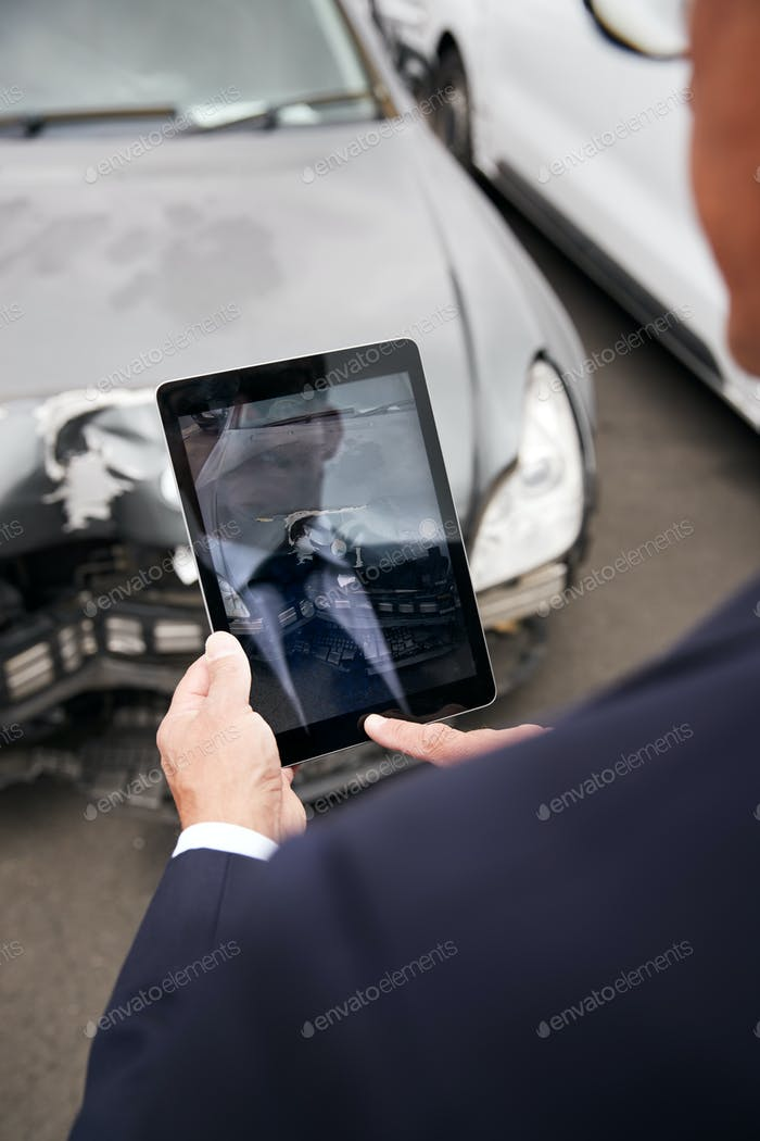Insurance Loss Adjuster Taking Picture With Digital Tablet Of Damage To Car From Motor Accident