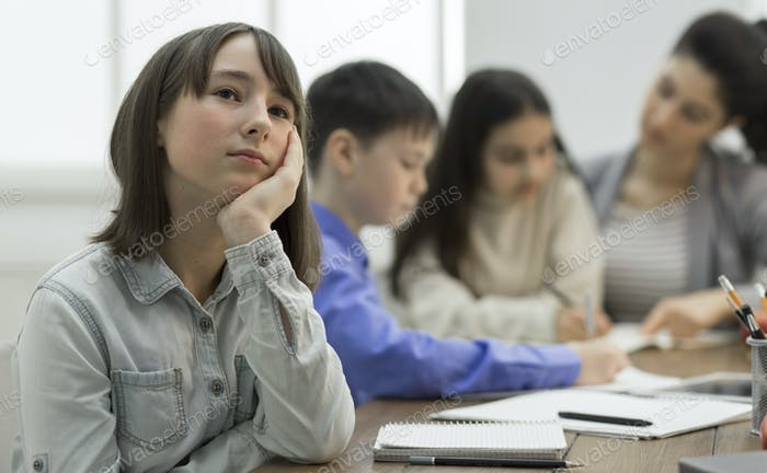 Bored girl sitting at lesson in classroom