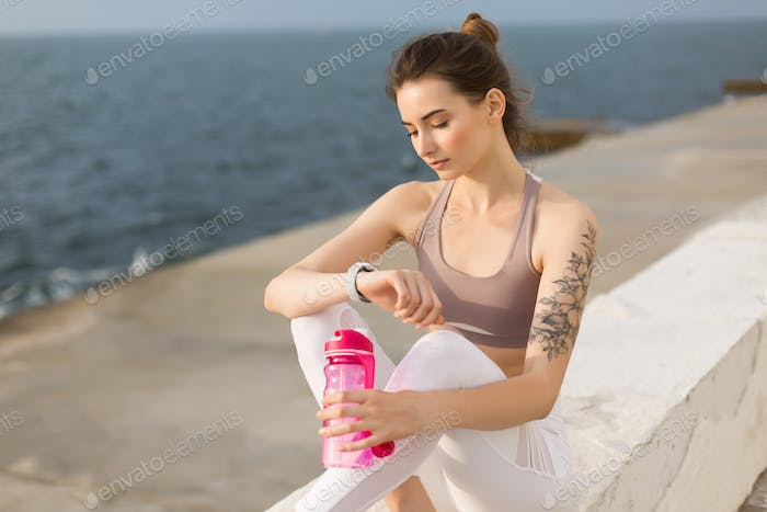 Young thoughtful woman in sporty top and white leggings holding