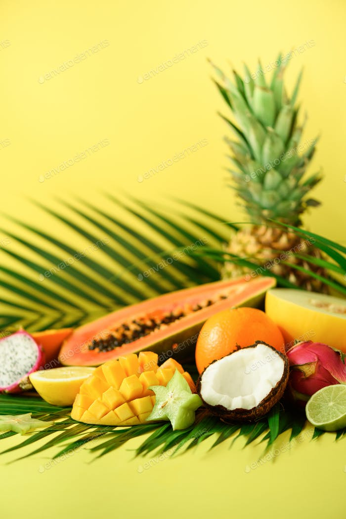 Assortment of exotic fruits on yellow background. Detox, vegan food, summer concept. Papaya, mango