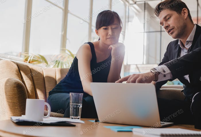 Business partners working together on laptop in office