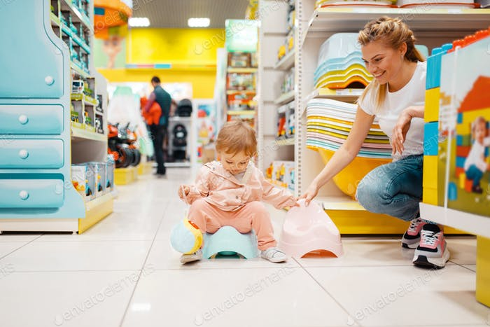 Mother with girl choosing baby potty in kids store