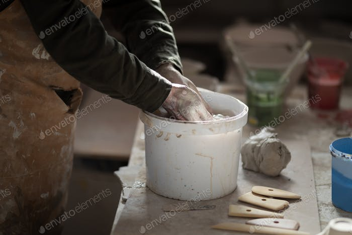 Mid section of male potter washing hands