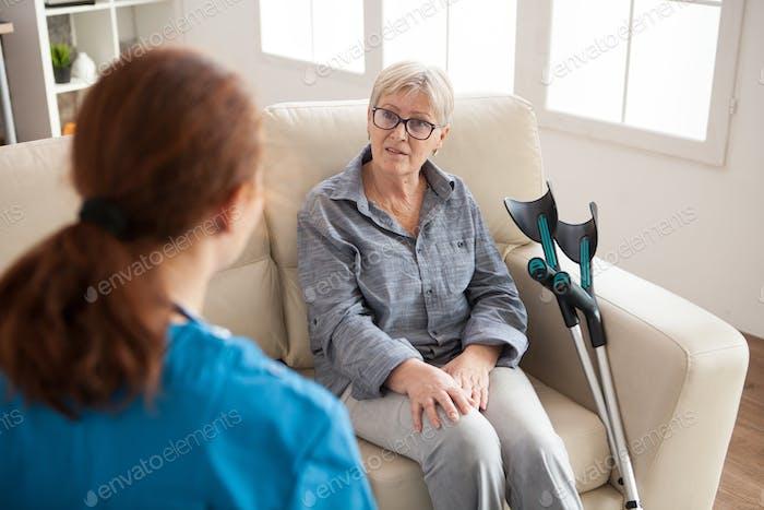 Вид сзади медсестры в доме престарелых разговаривает с женщиной-пенсионером