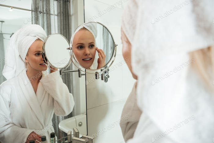 Young blonde woman looking in mirror to apply cosmetics