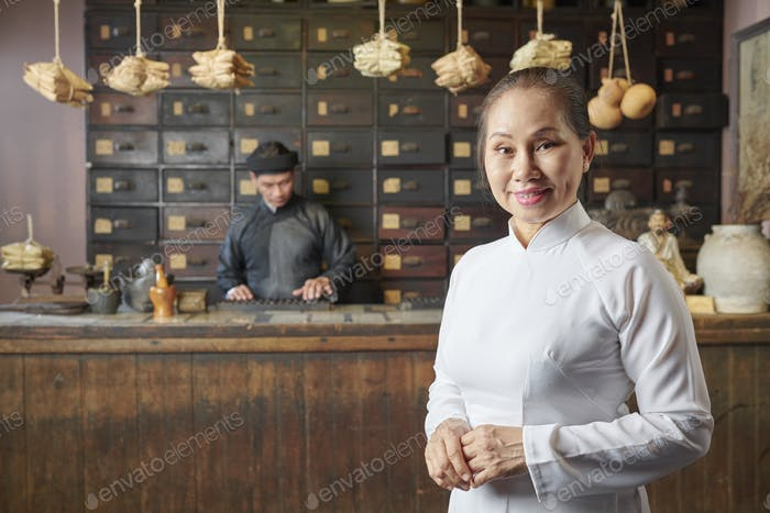 Aged woman at traditional Asian pharmacy