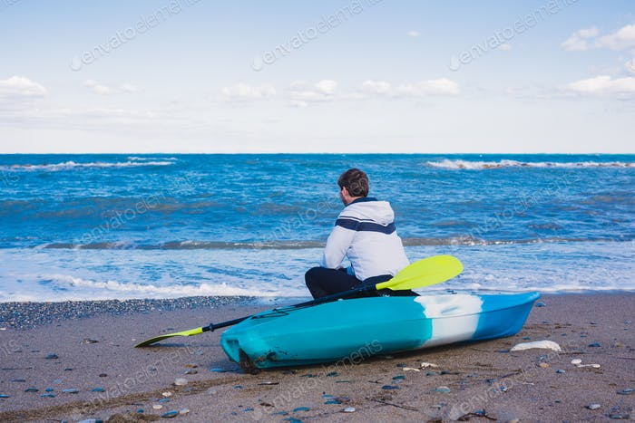 Man sitting on the beach with kayak