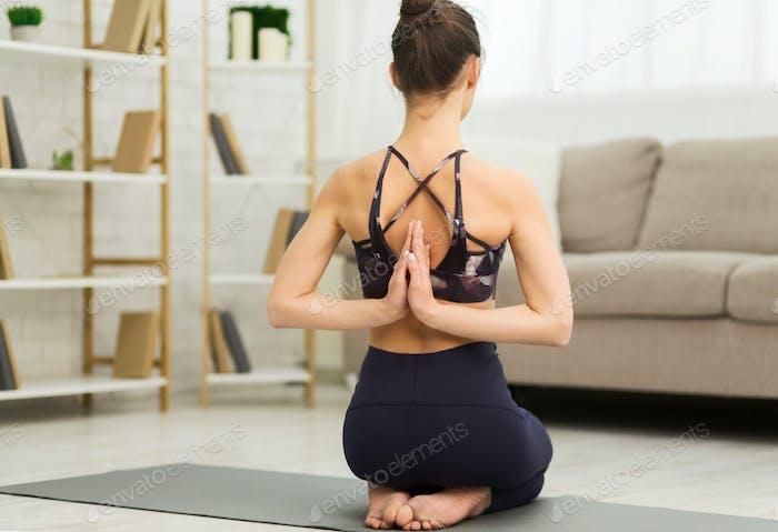 Young yogi woman making Namaste behind the back