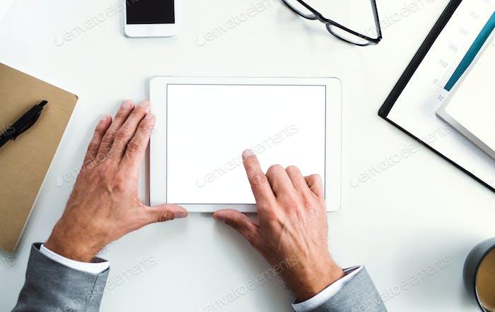 Ein Mittelteil des Geschäftsmanns sitzt am Tisch, mit Tablet. Eine Draufsicht. Kopierraum.