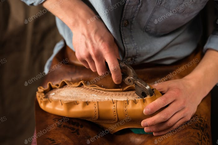 Bootmaker sitting in workshop making shoes