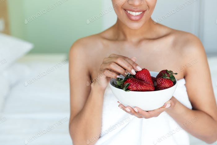 Cropped photo of cheerful young african woman eating strawberry.