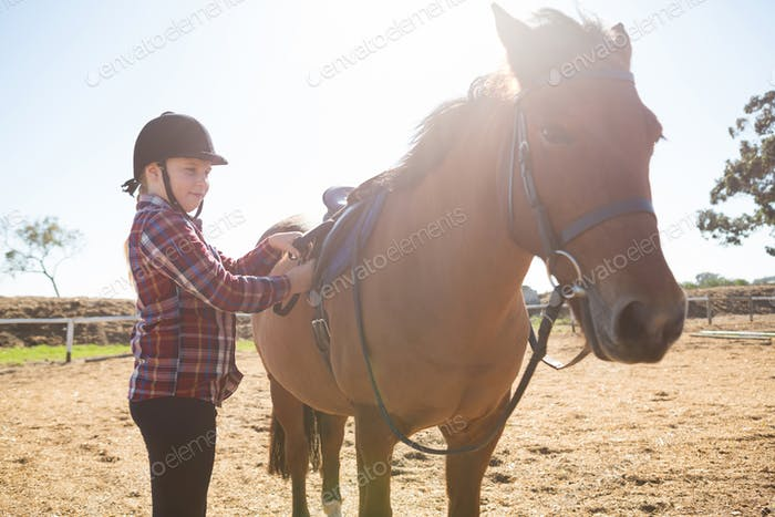 Girl adjusting saddle on horse in ranch