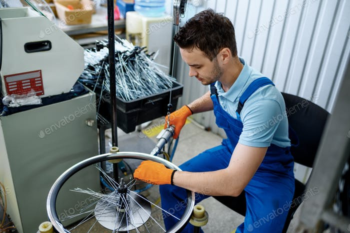 Worker with machine tool installs bicycle spokes