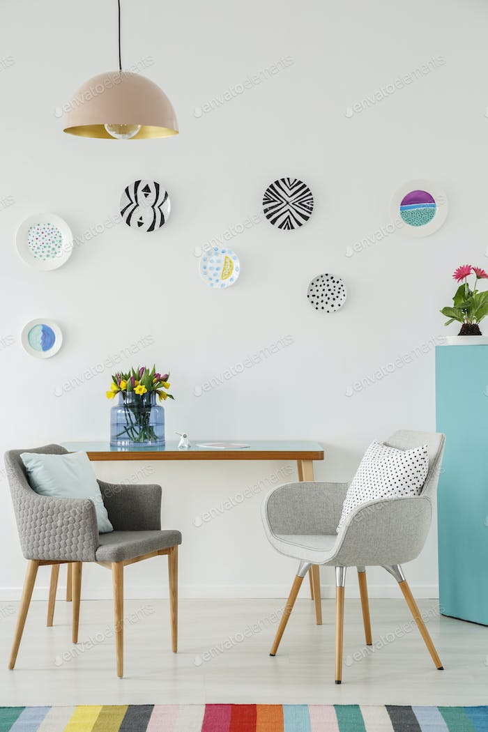 Creative living room interior with plates on the wall, table, gr
