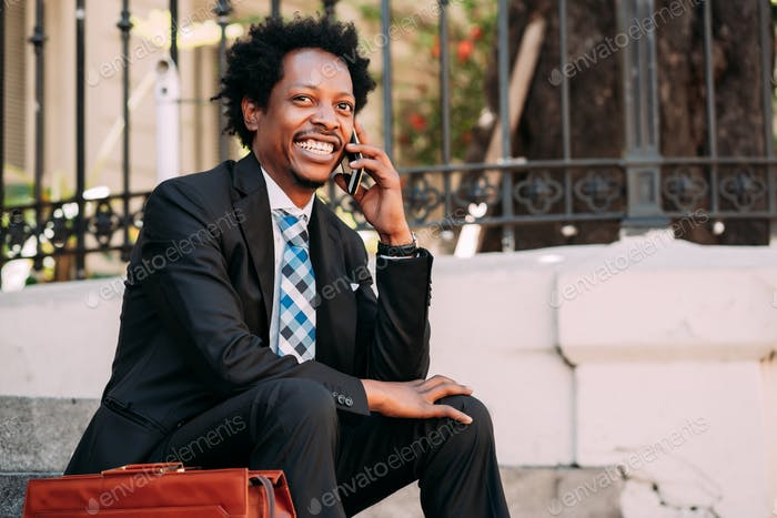 Businessman talking on phone outdoors.