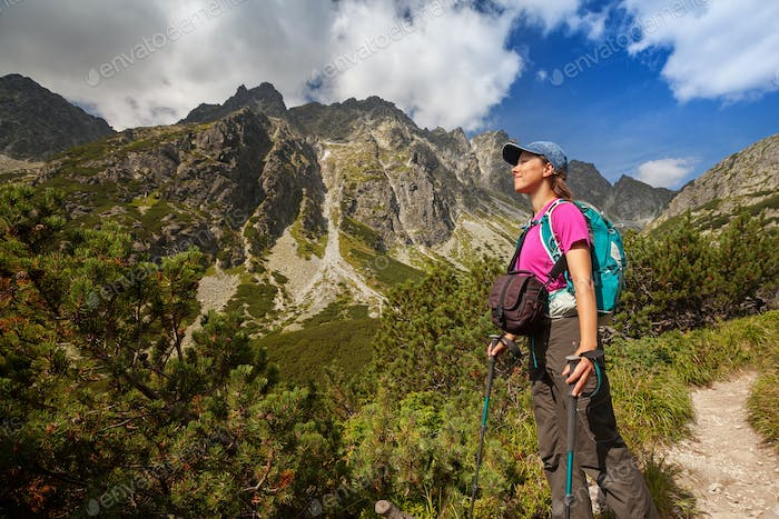 Hiking woman admiring the beauty of rocky mountains