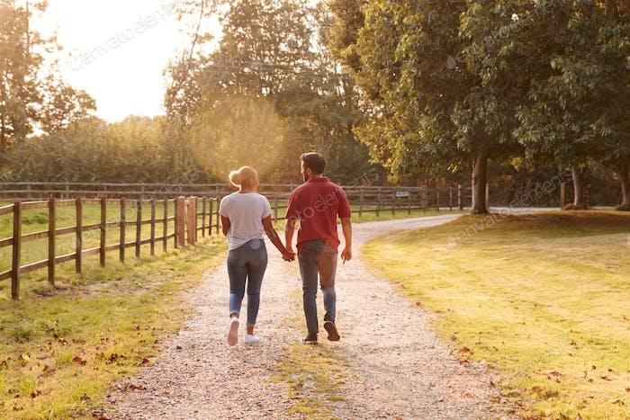 Rückansicht von Romantischen Paar Walking Hand in Hand entlang Land Lane bei Sonnenuntergang