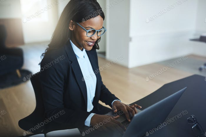 Smiling African American businesswoman working in her office