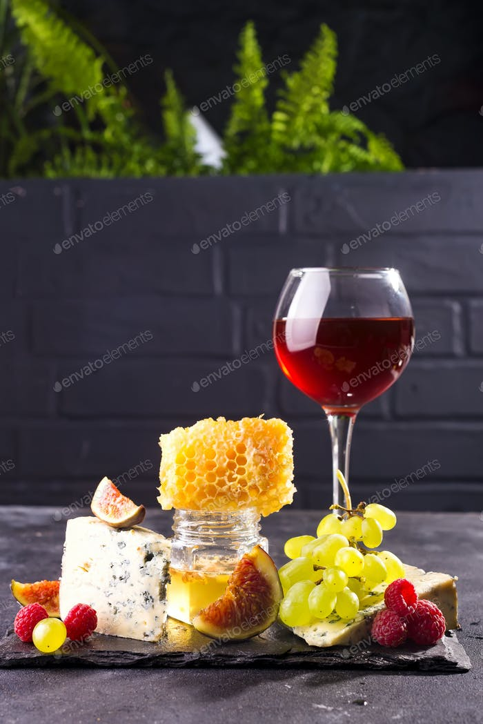 Assortment of cheese, berries and grapes with red wine in glasses on stone background. Copy space