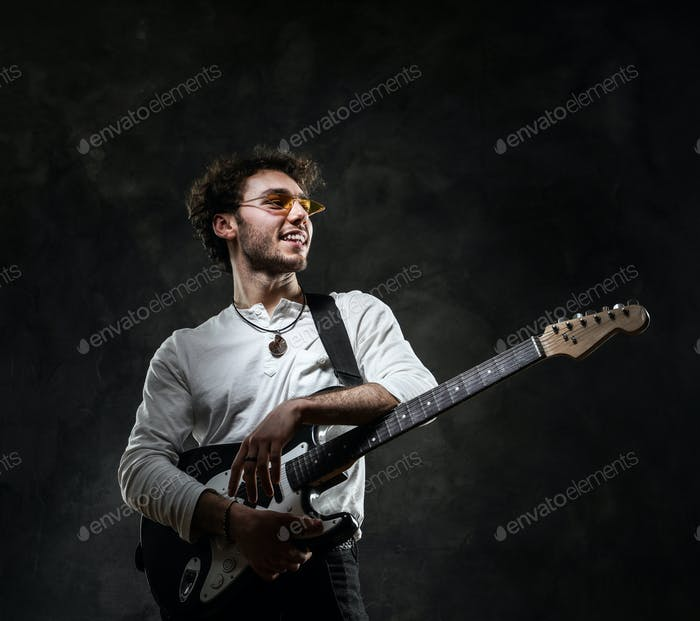 Smiling attractive male musician playing an electric guitar in a dark studio
