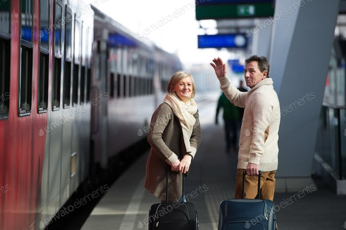Senior couple on train station pulling trolley luggage, waving.