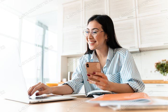 Happy brunette young woman using laptop computer
