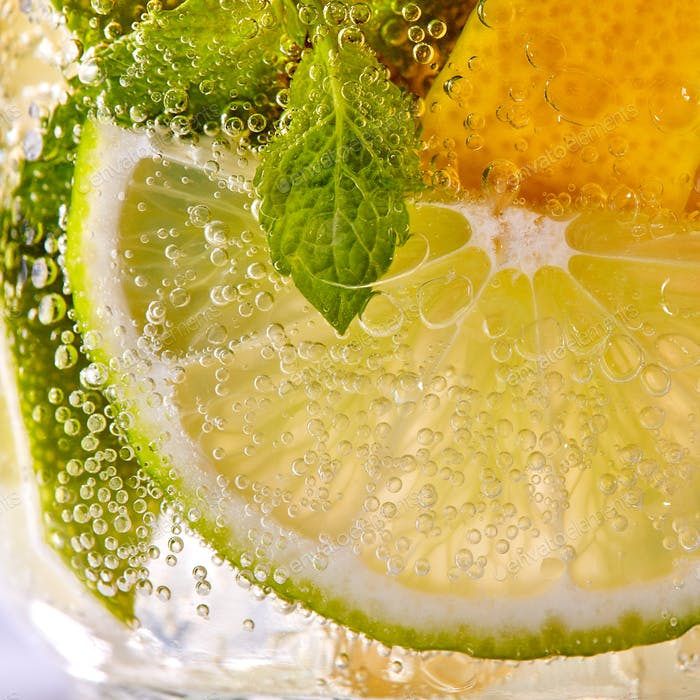 Macro photo of fresh slices of green lime, yellow lemon and mint leaf with bubbles in a glass