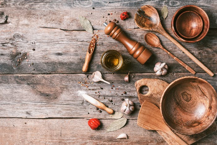 Wooden kitchen utensils on wooden background. Top view. Copy space. Food preparing concept. Bowls