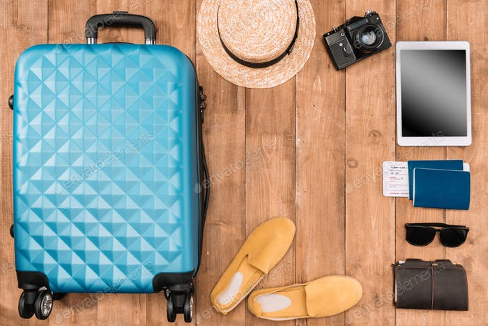 Summer vacation background with travel accessories. closed luggage, shoes, digital devices and