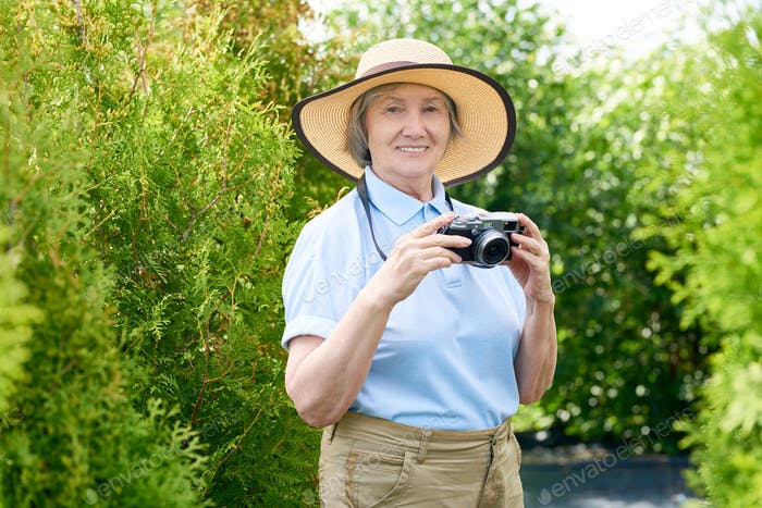 Happy Senior Woman Taking Pictures on Vacation