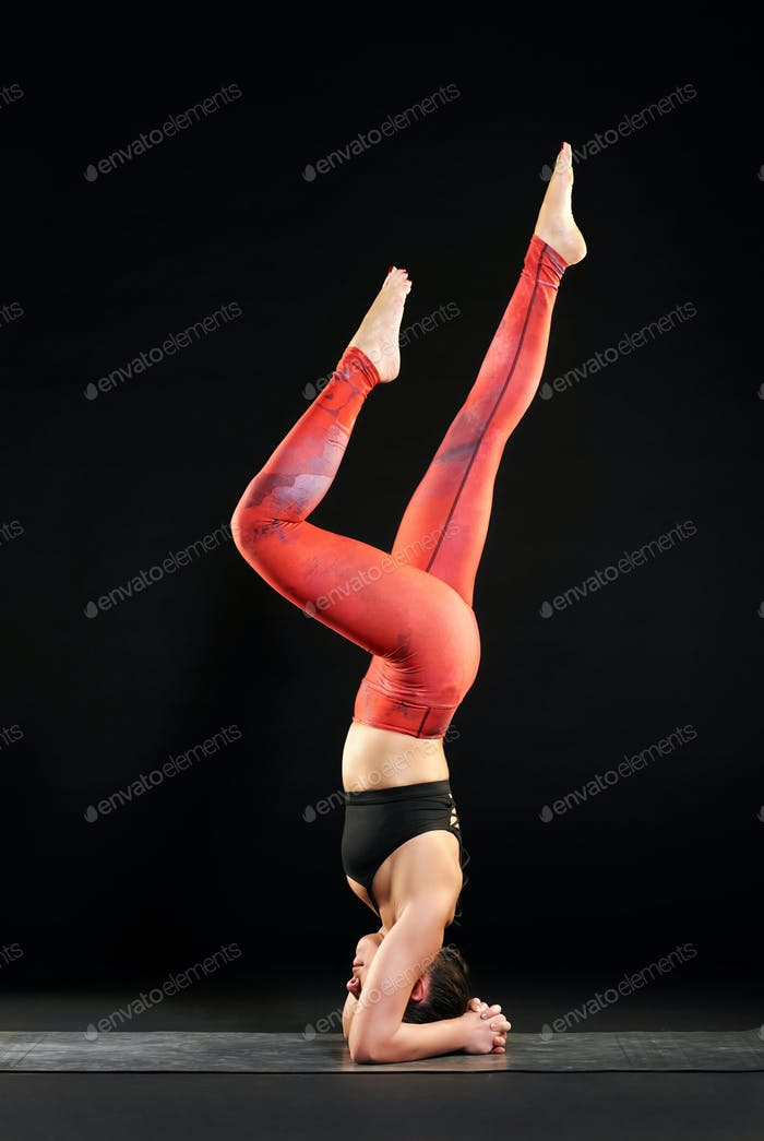 Woman working out on a yoga mat doing a headstand