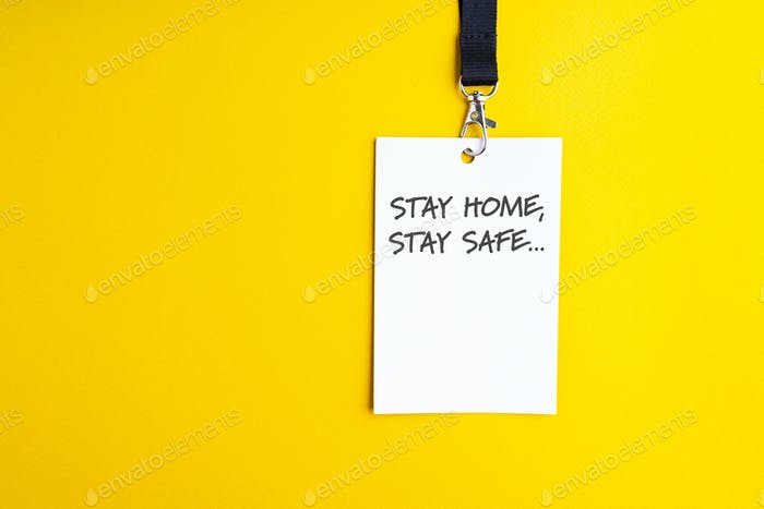 White paper bagde on yellow background lanyard with stay home stay safe sign