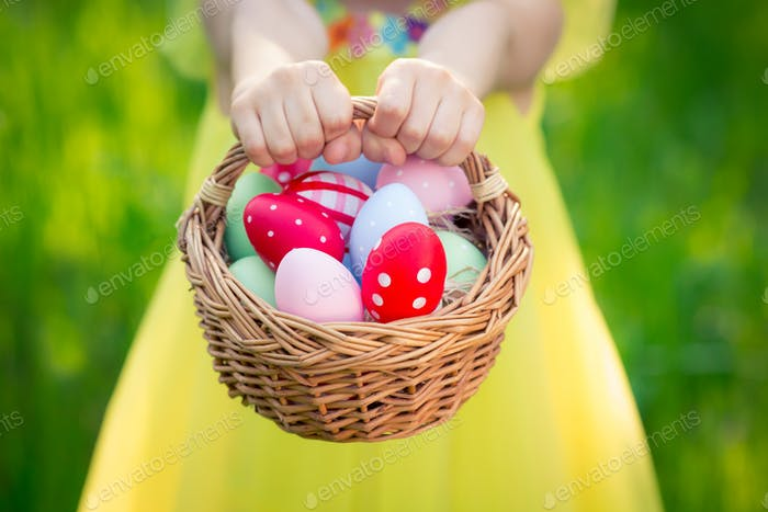 Child holding basket with Easter eggs
