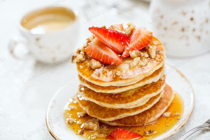 Pancakes with honey and strawberries