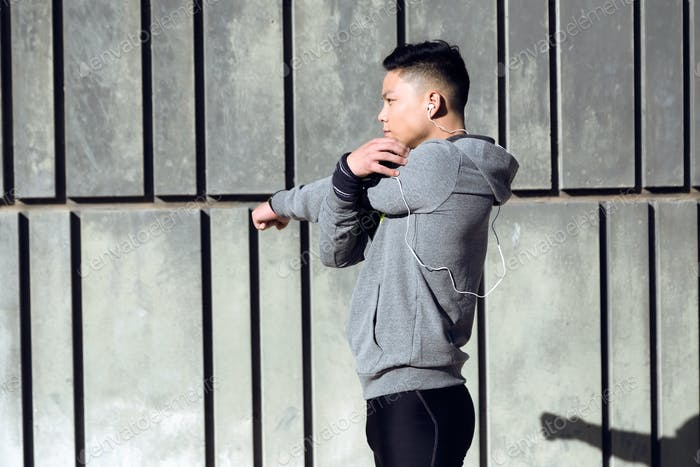 Fit and sporty young man doing stretching in city.