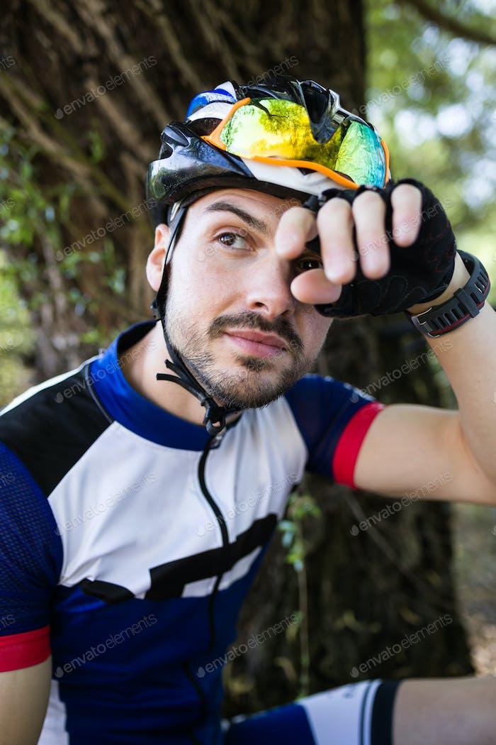 Joven guapo que se relaja después de montar en bicicleta en la montaña.