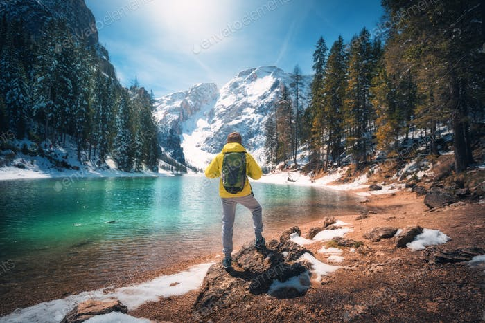 Man with backpack on the stone near lake with azure water