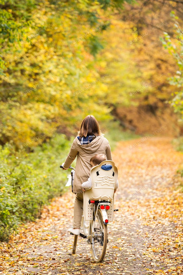 Young mother with son cycling in autumn park
