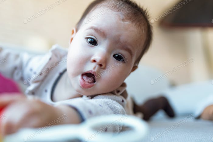 Cute baby girl looking at camera and playing with the rattle while lying down on sofa at home.