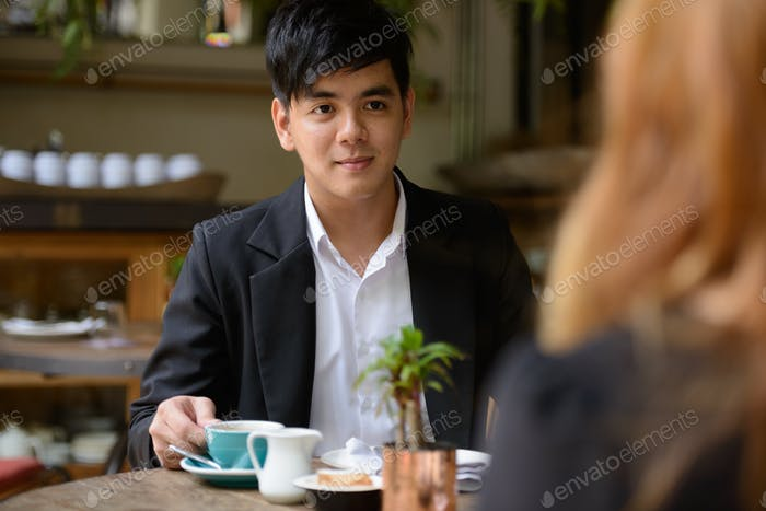 Young Asian business couple talking together at the coffee shop
