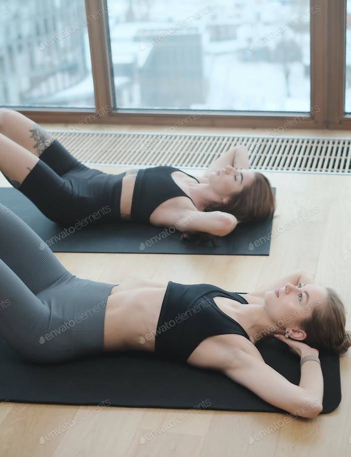 Caucasian girls with slim figure doing workout in modern room