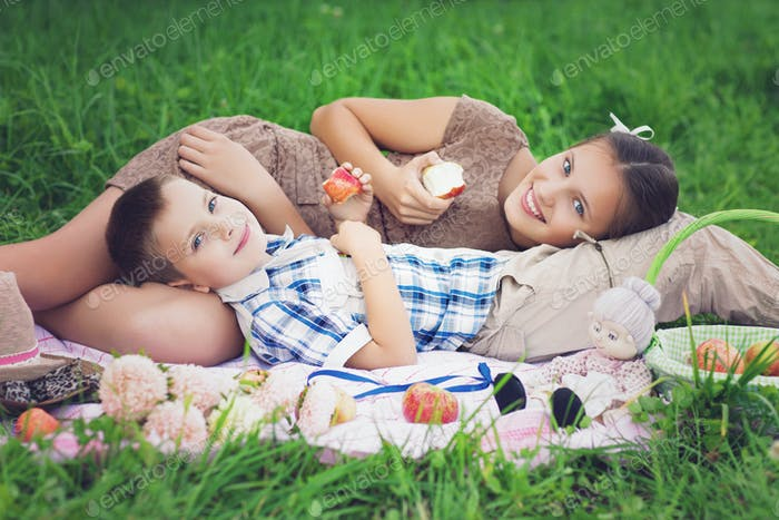 Little boy and teen age girl having picnic outdoors