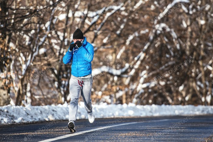 man running on a forest road and training for sports. Outdoor workout of jogger