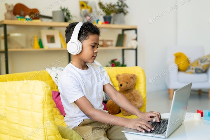 Diligent schoolboy of elementary age in headphones pushing laptop buttons