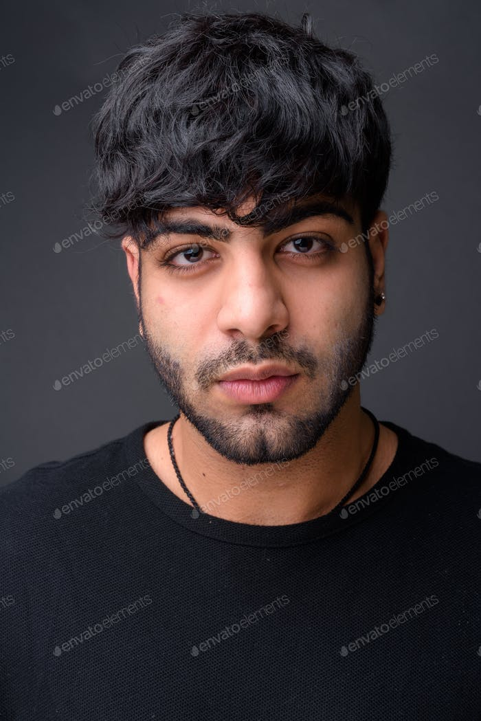 Young handsome Indian man against gray background