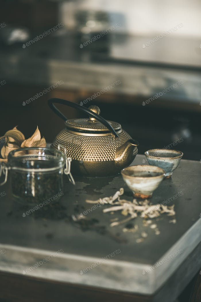 Golden iron teapot and japanese ceramic cups on kitchen counter